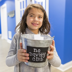 Little girl holding a no cavity bucket after completing her hygiene dental services